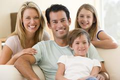 Family sitting in living room smiling Stock Photos
