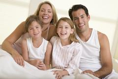 Family sitting in bed smiling Stock Photos