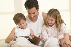 Man with two young children sitting in bed reading a book and smiling Stock Photos