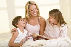 Woman with two young children sitting in bed reading book and smiling Stock Photos