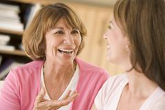 Two women sitting in living room talking and smiling Stock Photos