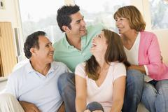 Two couples sitting in living room smiling and laughing Stock Photos