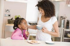 Woman and young girl in kitchen with cookies and coffee smiling - stock photo