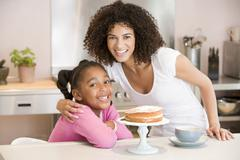 Woman and young girl in kitchen with cake and coffee smiling Stock Photos
