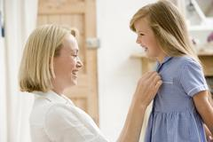Woman in front hallway fixing young girl's dress and smiling Stock Photos
