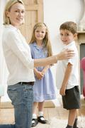 Woman in front hallway with two young children smiling Stock Photos