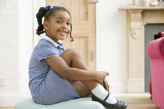 Young girl in front hallway fixing shoe and smiling Stock Photos