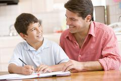 Man helping young boy in kitchen doing homework and smiling Stock Photos