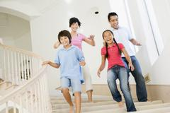 Family running down staircase smiling Stock Photos