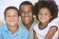 Man and two young children sitting in living room smiling - stock photo
