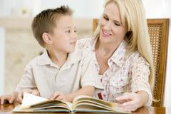 Woman and young boy reading book in dining room smiling Stock Photos
