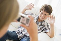 Young girl taking picture of smiling young boy with camera phone indoors Stock Photos