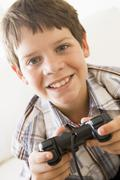 Young boy holding video game controller smiling - stock photo