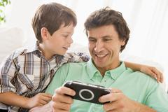 Man and young boy with handheld game smiling - stock photo