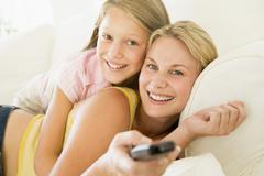 Woman and young girl with remote control embracing on sofa smiling - stock photo