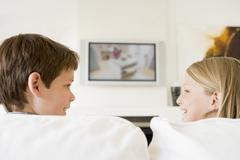Young boy and young girl in living room with flat screen television Stock Photos