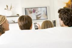 Family in living room with remote control and flat screen television - stock photo