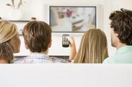 Stock Photo of Family in living room with remote control and flat screen television