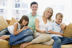 Family sitting in living room with remote control smiling Stock Photos