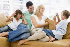 Family sitting in living room with digital camera smiling - stock photo