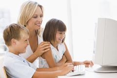 Woman and two young children in home office with computer smiling Stock Photos
