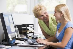 Woman and girl in home office with computer smiling - stock photo