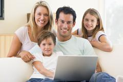 Family in living room with laptop smiling Stock Photos