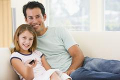 Man and young girl in living room with remote control smiling - stock photo