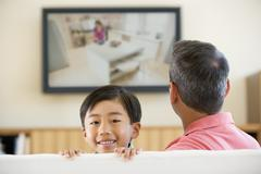 Man and young boy in living room with flat screen television smiling Stock Photos