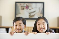 Two young children in living room with flat screen television smiling - stock photo