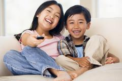 Two youngchildren in living room with remote control smiling Stock Photos