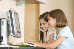 Two young girls in kitchen with computer smiling Stock Photos