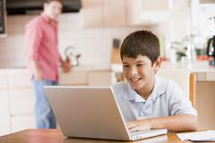 Young boy in kitchen with laptop and paperwork smiling with man in background Stock Photos