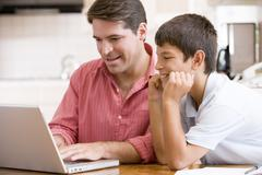Man helping young boy in kitchen with laptop smiling - stock photo