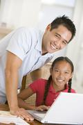 Man and young girl with laptop in dining room smiling Stock Photos
