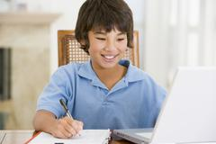 Young boy with laptop doing homework in dining room smiling Stock Photos