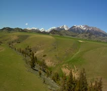 Aerial shot of grassy vallet, snowy mountains in distance Stock Footage