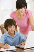 Woman helping young boy with laptop do homework in dining room smiling Stock Photos