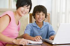 Woman helping young boy with laptop do homework in dining room smiling - stock photo