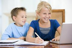 Two young children with laptop doing homework in dining room smiling - stock photo
