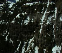 Stock Video Footage of Aerial shot of craggy snow-covered mountain cliffs