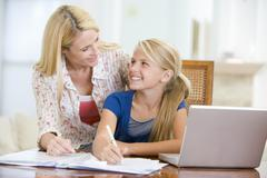 Woman helping young girl with laptop do homework in dining room Stock Photos