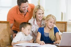 Couple helping two young children with laptop do homework in dining room Stock Photos