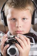 Young boy wearing headphones in bedroom holding many electronic devices Stock Photos