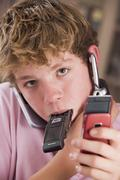 Young boy in bedroom holding many cellular phones Stock Photos