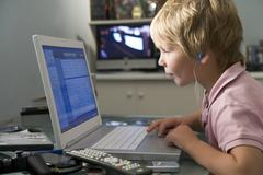 Young boy in bedroom using laptop and listening to MP3 player Stock Photos