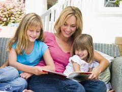 Woman and two young girls sitting on patio reading book smiling - stock photo