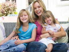 Woman and two young girls sitting on patio smiling - stock photo