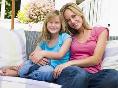 Woman and young girl sitting on patio smiling - stock photo
