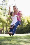 Stock Photo of Woman and young girl outdoors on tree swing smiling